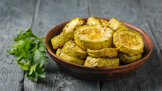 Baked zucchini slices in a clay bowl on a black wooden table. vegetarian dish. natural plant food.