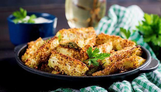 焼きズッキーニには、チーズとパン粉が付いています。ビーガンフードベジタリアン料理。