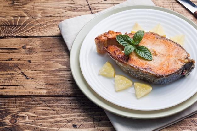 レモンと皿の上の焼き魚のbakedのステーキ。木製テーブル。