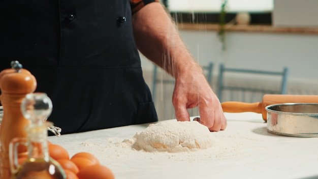 Baker adding flour on the pile by hand preparing bread dough. close up of retired elderly chef with bonete and uniform sprinkling, sieving spreading rew ingredients baking homemade pizza and cackes.