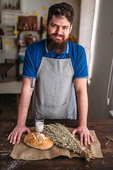 サクサクした皮が付いている焼きたてのパンのパン、小麦の束、黄麻布の牛乳のガラスに対するパン屋。自家製ベーカリーコンセプト、自然の有機食品。