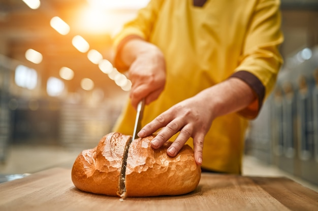 A baker at a bakery factory cuts freshly baked bread with a knife.
