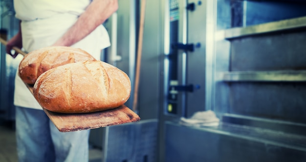 Baker in bakery with bread on shovel