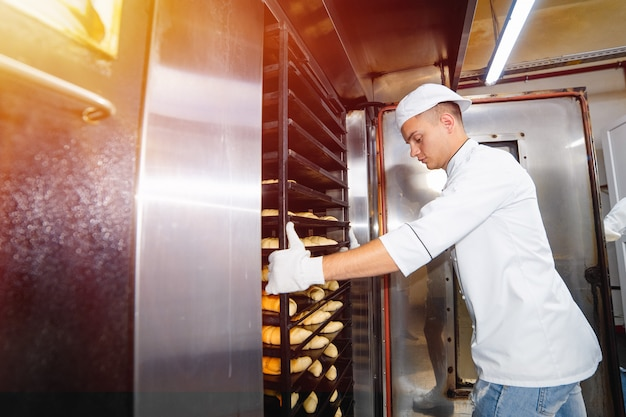Baker boy inserts a cart with raw dough baking trays into an industrial oven in a bakery.