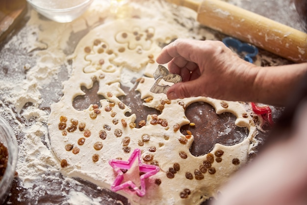 Baker cropping out cookie shapes out of sheet of dough