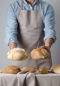 Baker in a denim shirt holds out two breads