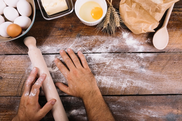 Baker dusting with flour on wooden table with baked ingredients