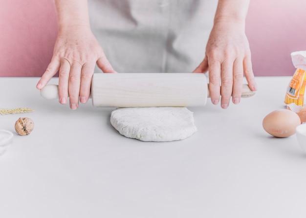 Baker flattening dough with rolling pin