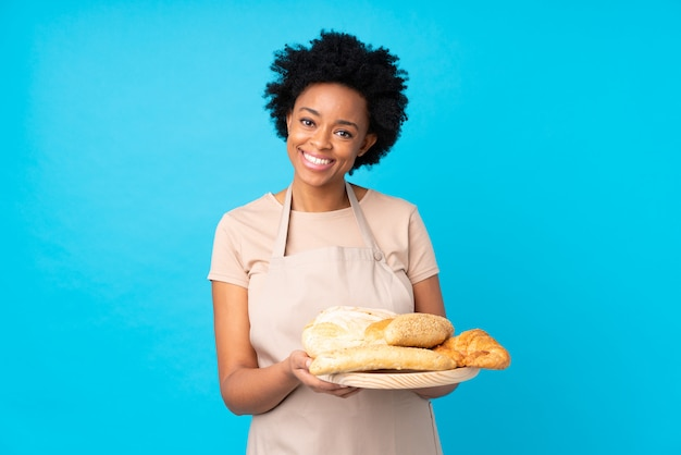 Baker girl catching breads over blue background