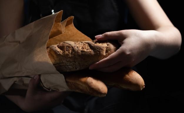Девушка-пекарь достает свежий хлеб из бумажного пакета. темный фон