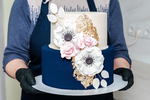 おいしいお祭りケーキのクローズアップを保持しているパン屋の手