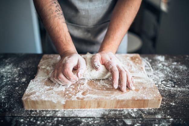 Пекарь руками замешивает тесто с мукой