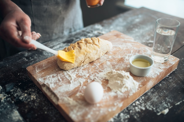 베이커 손에 빵 반죽에 버터가 묻어 있습니다. 커팅 보드에 빵 준비. 수제 신선한 베이커리