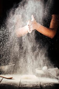 Пекарь руки посыпают приготовление пиццы муки