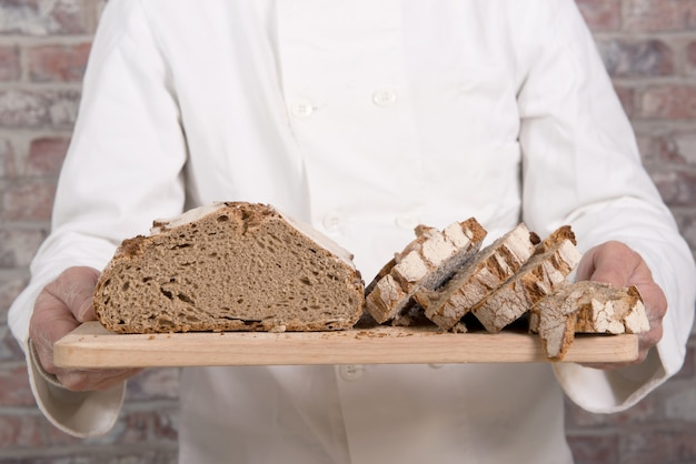 Baker hands with fresh bread on wood table