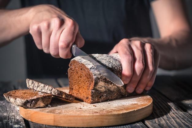 Пекарь держит в руках свежий хлеб