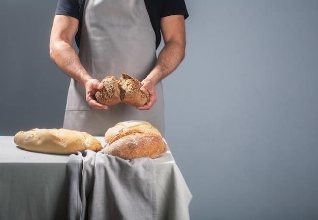회색 배경에 테이블 위에 갓 구운 된 빵을 들고 베이커