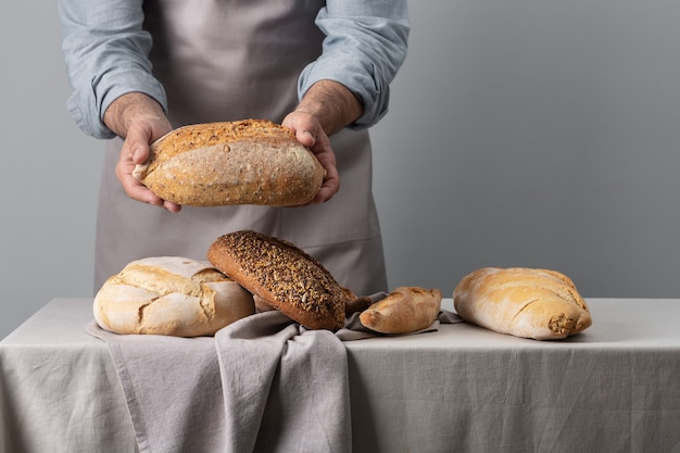 Baker holding freshly baked bread over table on gray background with copy space