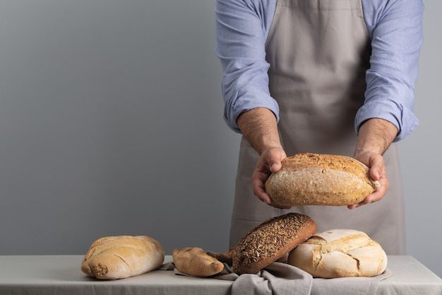 Baker holding freshly baked bread over table on gray background