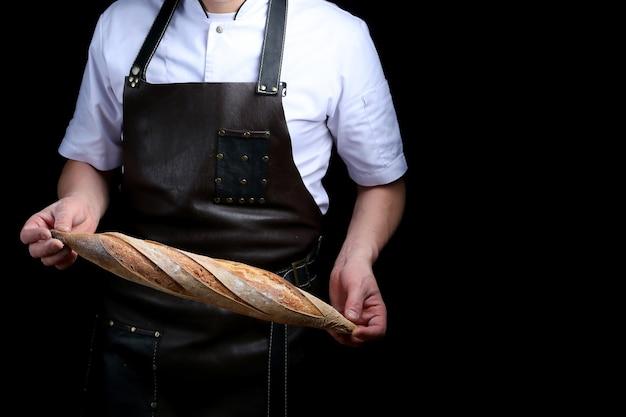 Baker holds baguette isolated on black background