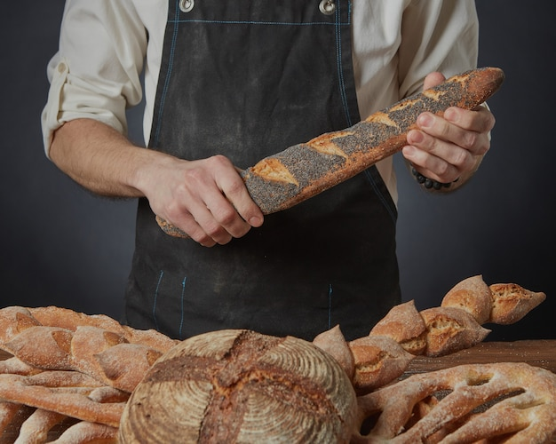 Baker holds a baguette with poppy seeds on a dark background and a variety of bread on the table