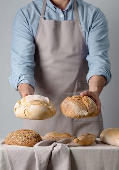 데님 셔츠를 입은 베이커가 빵 두 개를 들고
