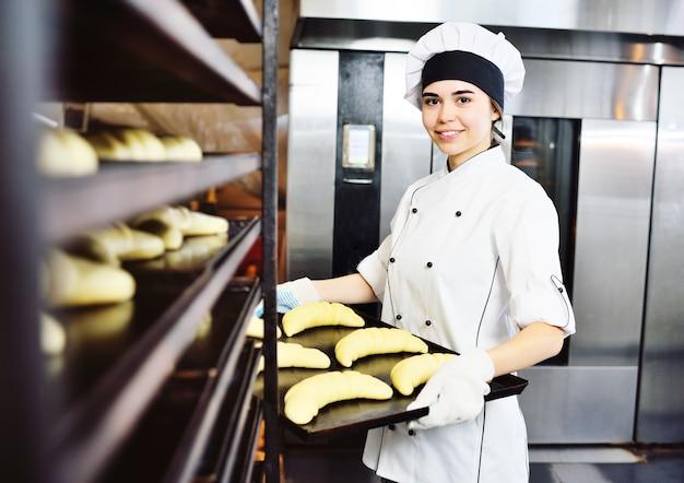 白いシェフのジャケットと帽子をかぶったパン屋は、生のクロワッサンが入ったベーキングトレイを持っています