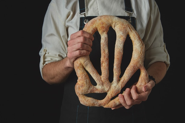 エプロンのパン屋は、自家製の有機フーガスパンを手に持っています