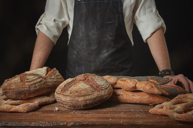 木製の茶色のテーブルに焼きたてのパンとエプロンのパン屋