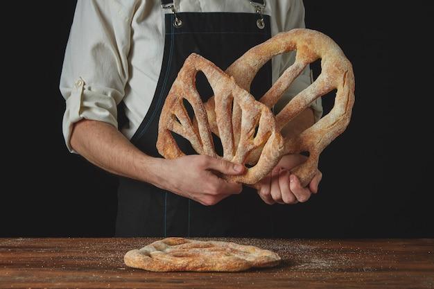 エプロンのパン屋は暗い背景に焼きたてのフーガスパンを保持します