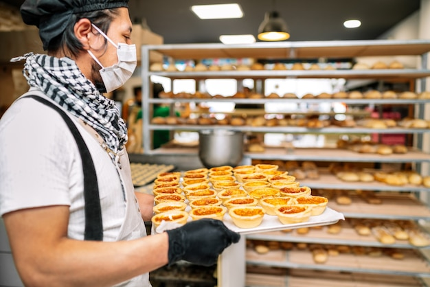 Baker is holding a tray of rice cake fresh from the oven and is leaving it on a tray cart to be sold at the bakery and is wearing a face mask
