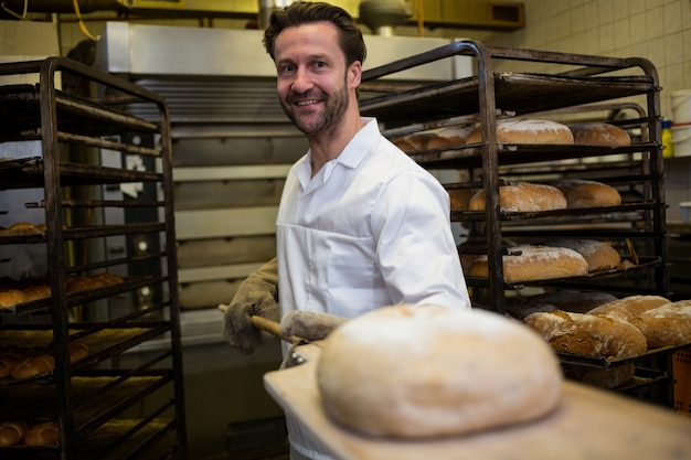 Baker keeping baked bread on counter