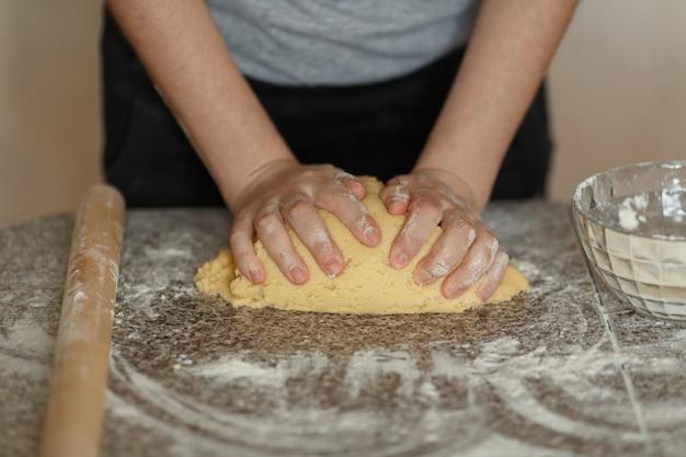 テーブルの上で小麦粉で生地をこねるパン屋。