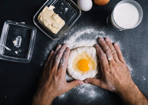 Baker kneading dough with egg york on kitchen counter