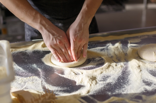 Baker kneads dough for pizza in the kitchen in the restaurant