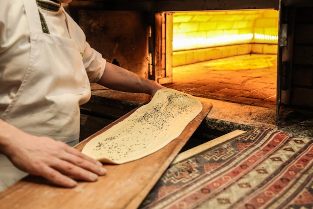 Baker makes some bread in oven