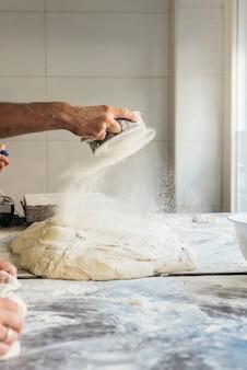 小麦粉を生地に広げるパン屋さんの手。ベーカリーコンセプト。