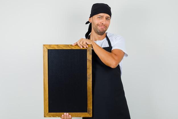 Uomo del panettiere che tiene la lavagna in maglietta