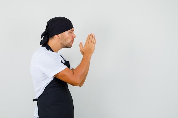 Uomo del panettiere che tiene le mani nel gesto di preghiera in maglietta