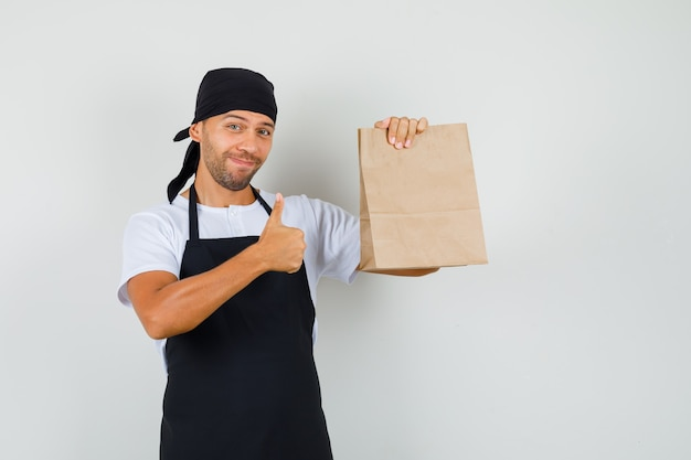 Baker man holding paper bag, showing thumb up in t-shirt