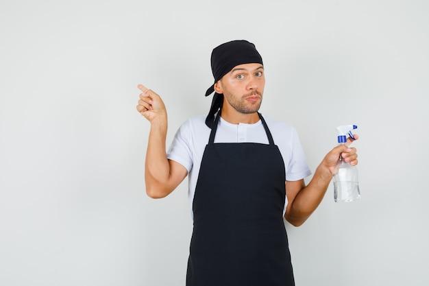 Uomo del panettiere che tiene la bottiglia dello spruzzo, che indica via in maglietta, vista frontale del grembiule.