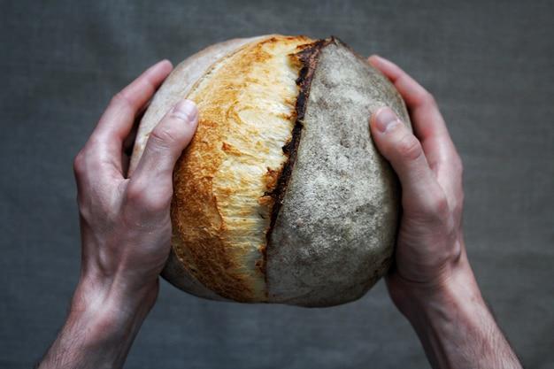 Бейкер мужчина держит белый хлеб на закваске домашний хлеб еда фотография