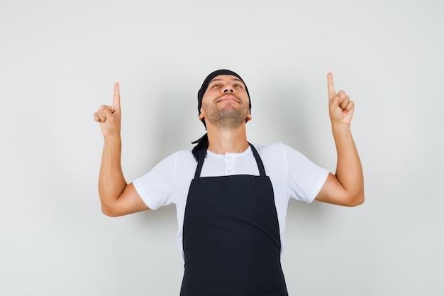 Tシャツ、エプロンで指を上に向けて感謝しているベイカーの男。