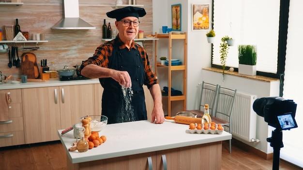 Мужчина-пекарь ведет кулинарный видеоблог, пока готовит домашнюю пиццу. блогер на пенсии, повар, влиятельный человек, используя интернет-технологии, общается и ведет блог в социальных сетях с помощью цифрового оборудования.