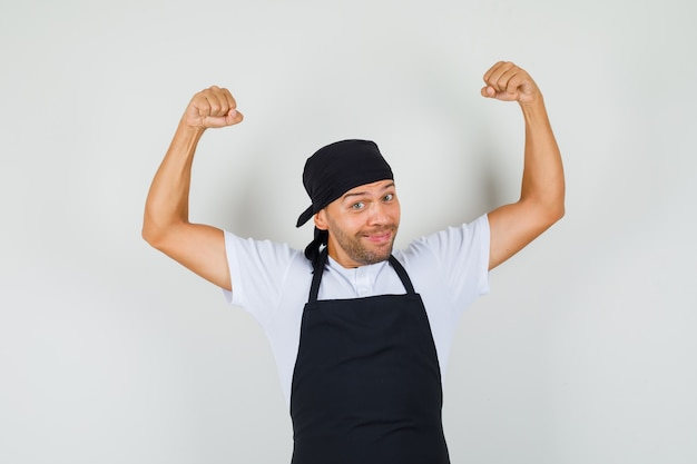 Baker man showing his muscles in t-shirt, apron and looking cheerful.