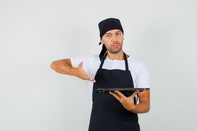 Uomo del panettiere che mostra vassoio metallico in maglietta