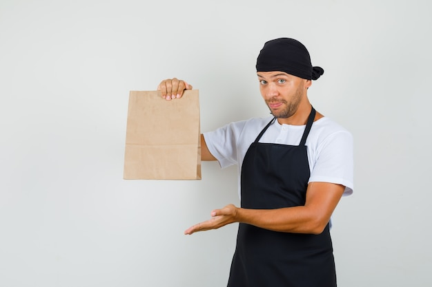 Baker man showing paper bag in t-shirt