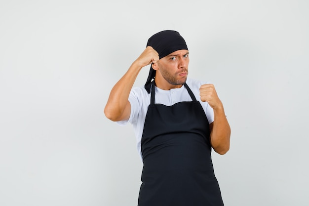 Baker man standing in boxer pose in t-shirt, apron and looking strong