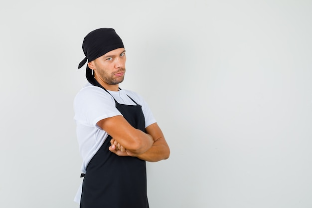 Uomo del panettiere in piedi con le braccia incrociate in maglietta, grembiule e che sembra serio.
