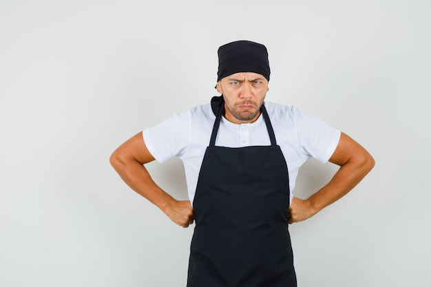 Uomo del panettiere in piedi con le mani sulla vita in t-shirt, grembiule e sguardo rabbioso
